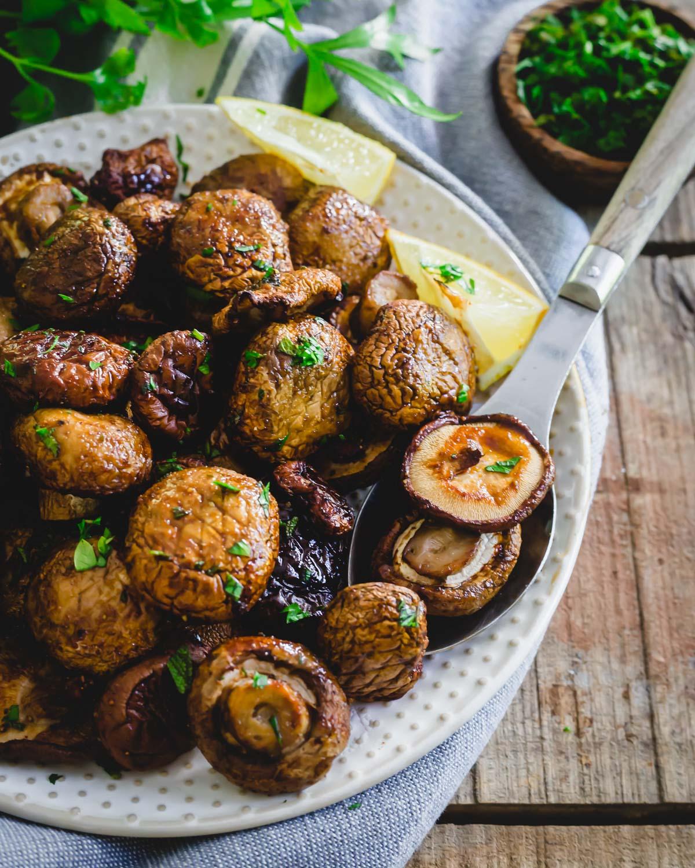 Garlic tamari seasoned whole air fryer mushrooms on a serving spoon.