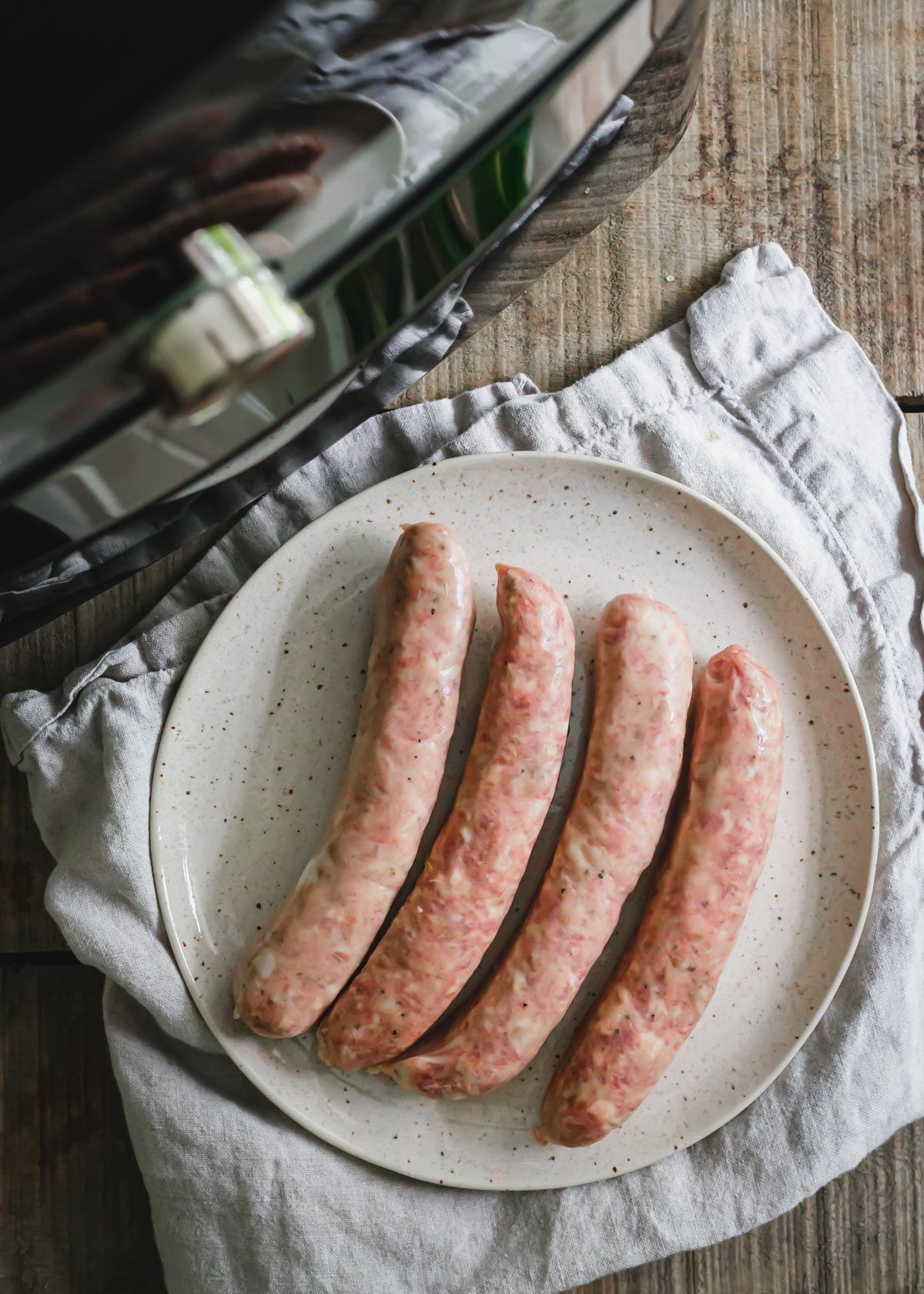 Uncooked pork sausage links on a plate before air frying.