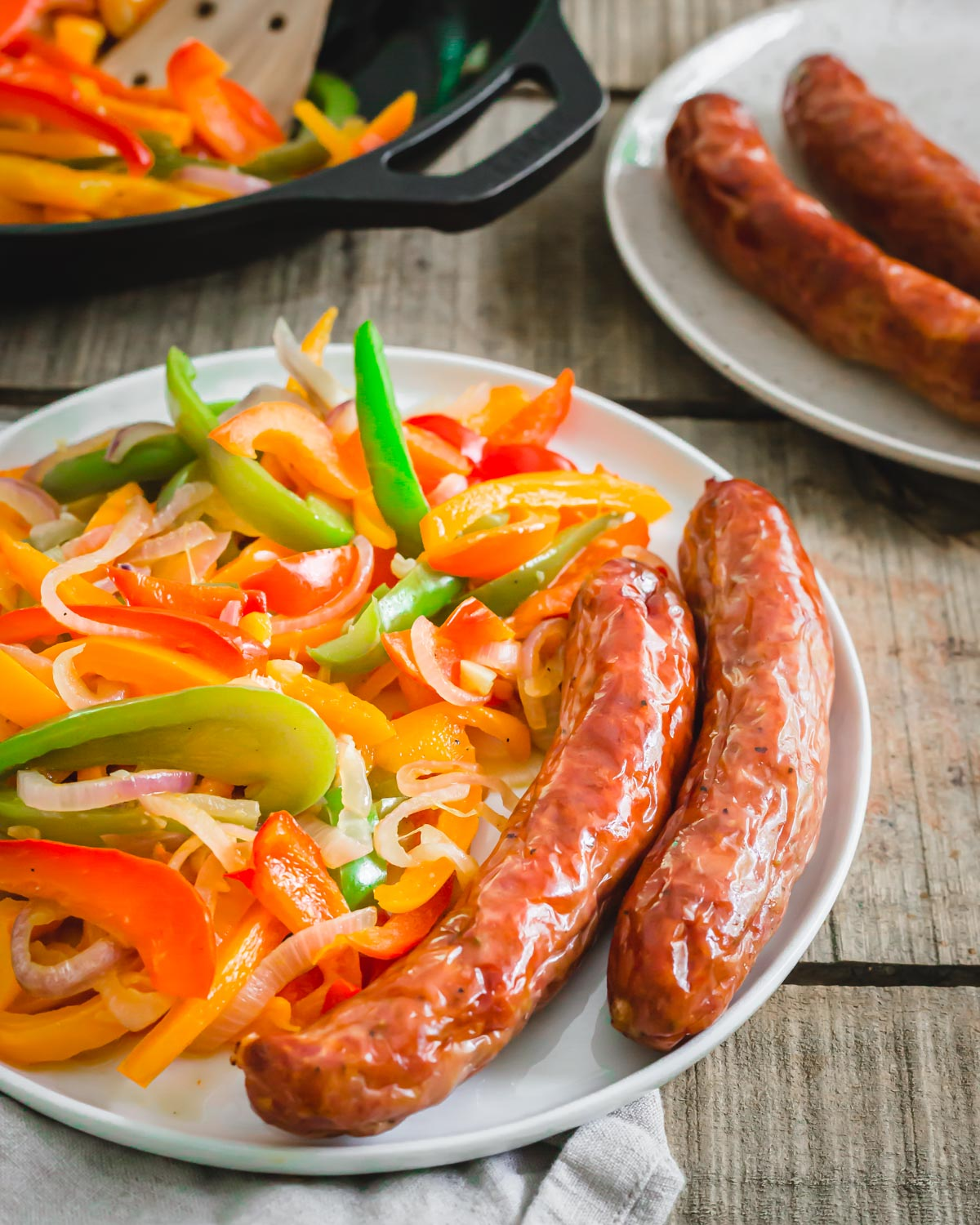 Air fryer Italian sausage served with peppers and onions on a plate.