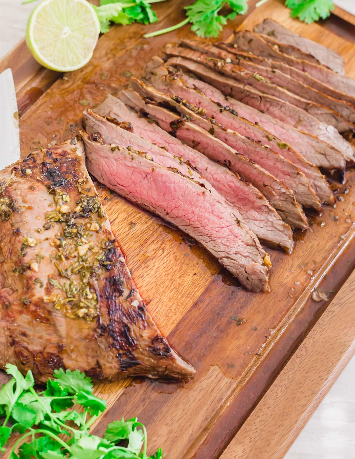 Grilled carne asada flank steak sliced on a cutting board.