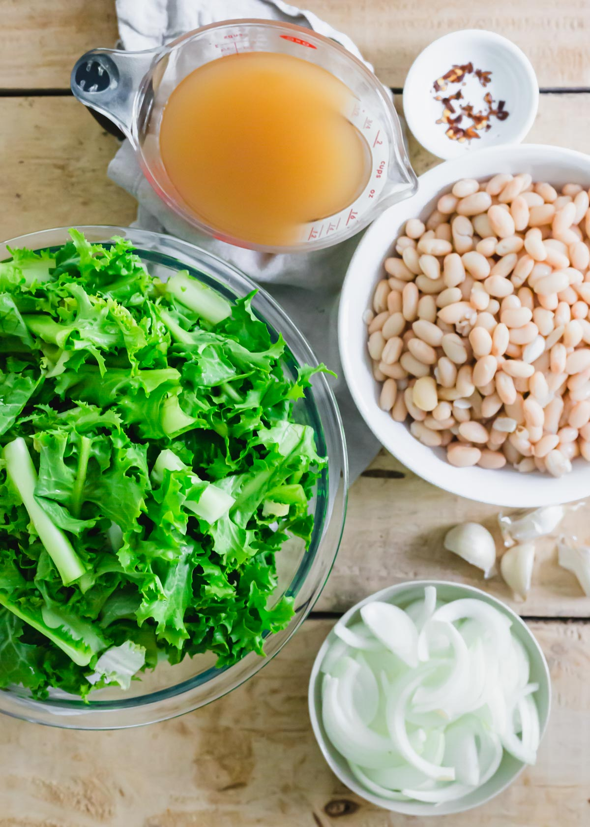 Ingredients to make the Italian dish of escarole and white beans.