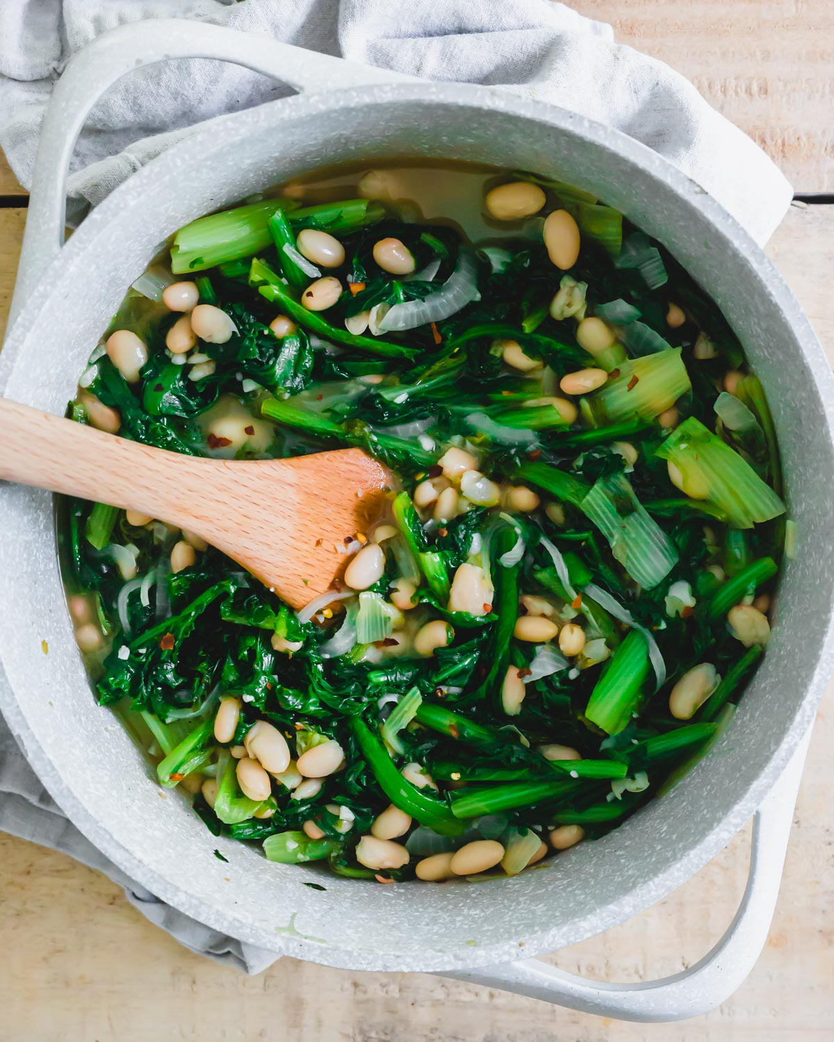 Escarole and beans in a pot with spatula.