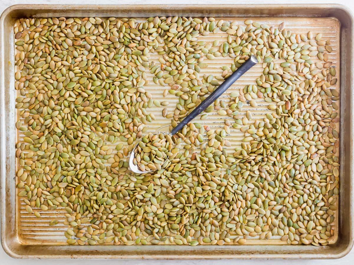 Roasted pepitas on a baking sheet.