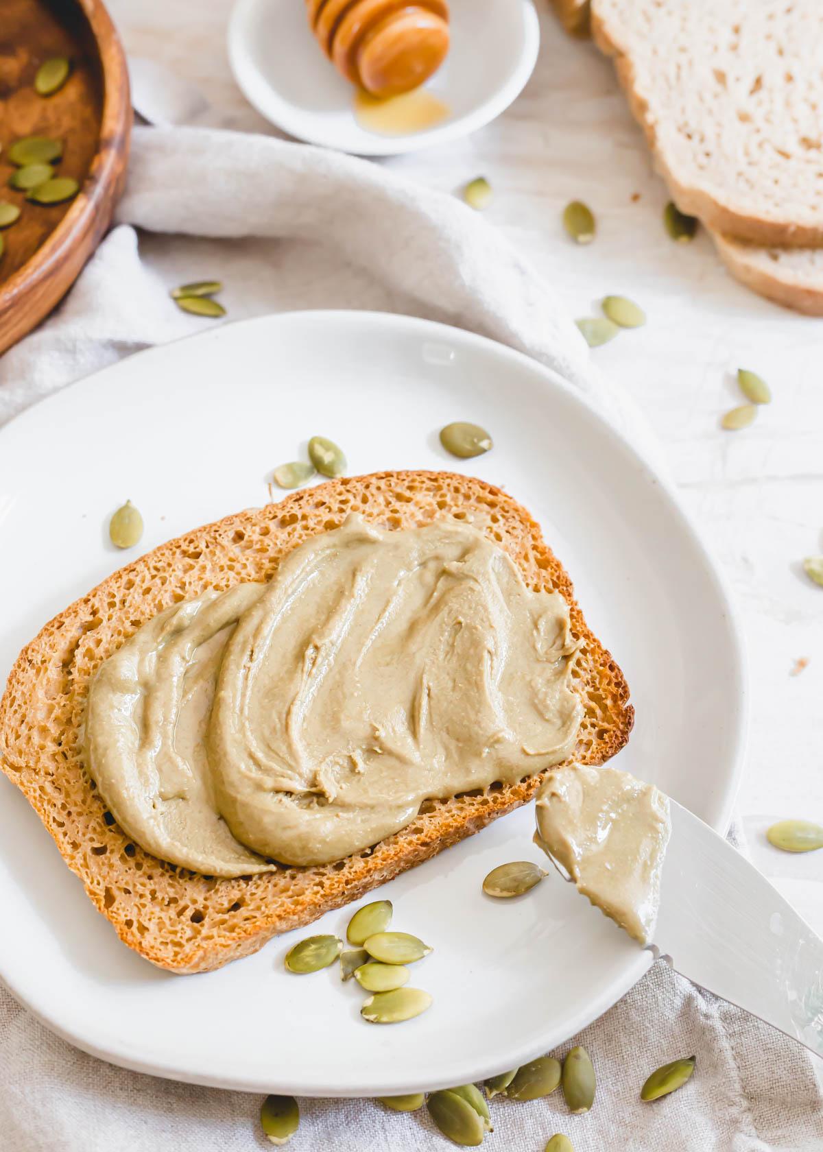 Spreading healthy pumpkin seed butter on gluten-free sourdough toast.